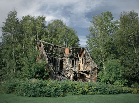 Ruins of an old abandoned rural house among trees. photo