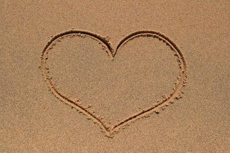 coast line: Heart symbol drawn in the sand beach.