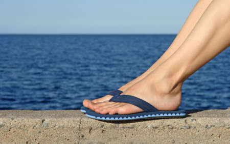 sandal: Female feet in blue flip-flops with see in the background.