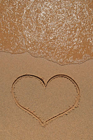 Wave running over the sand beach with heart drawing. photo