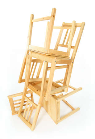 heap: Stacked wooden chairs on white background. Stock Photo
