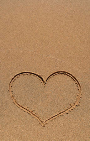 Heart symbol drawn in the sand beach, with copy-space. photo