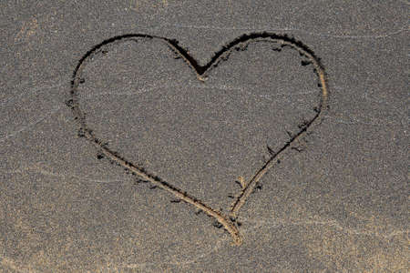Heart symbol drawn in the black sand beach. Stock Photo - 4306388