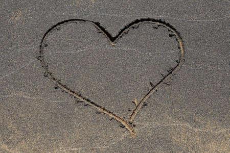 Heart symbol drawn in the black sand beach. photo