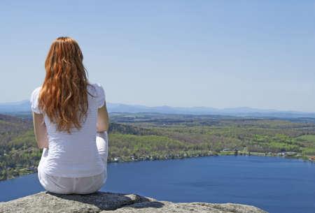 景色を楽しみ、山の上に座っている若い女性。