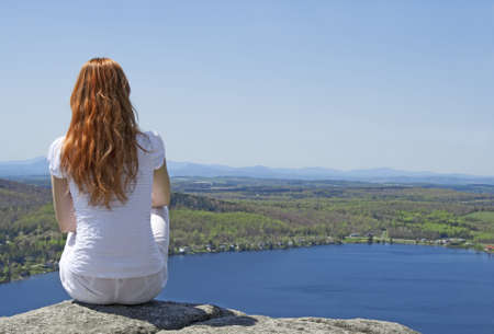 long lake: Young woman sitting on top of a mountain, enjoying the view. Stock Photo