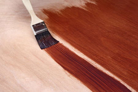 Painting a wooden surface with brown paint. photo