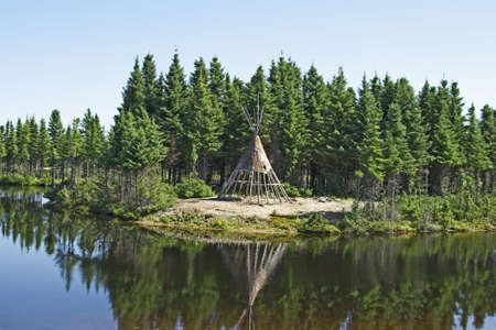 tipi: Traditional Native American tipi on a lakeshore.