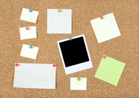 Post-it notes of different sizes and a blank photo pinned to corkboard. photo