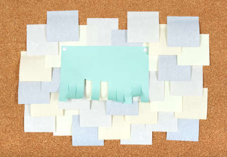 Blank ad with cut slips and many post-it notes on corkboard. photo
