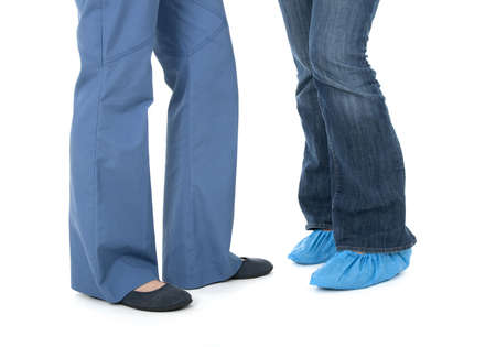 protectors: Legs of nurse in uniform and patient wearing shoe protectors. Stock Photo