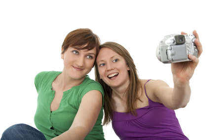Two young women taking a self-portrait with a digital camera. photo