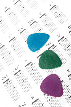 sheetmusic: Three guitar picks on of different colors a chords chart. Stock Photo