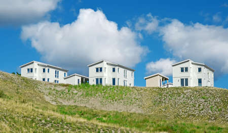 Newly built houses under the blue sky with huge white clouds. photo