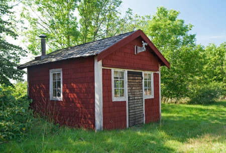 Wooden cabin in a forest painted in traditional Swedish brown color. Stock Photo - 5751157