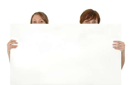 Two young women behind a blank banner ad, on white background. photo