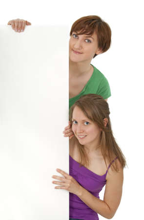 Two friendly young women in colorful clothes holding a blank banner ad. photo