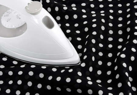 smoothen: Ironing delicate black and white polka fabric. Stock Photo