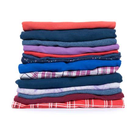 ropa casual: Pila de ropa casual multicolor sobre fondo blanco.  Foto de archivo