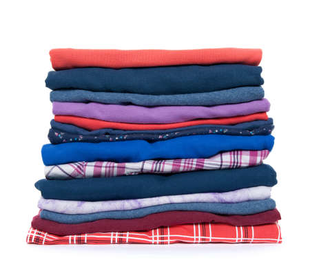fold: Pile of multicolored casual clothes on white background. Stock Photo