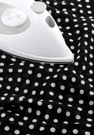 smoothen: Ironing delicate black and white silky fabric.