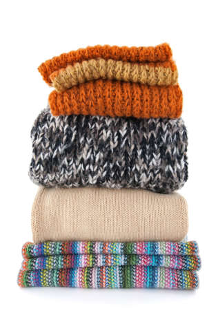 Pile of warm wool clothes on white background. Imagens
