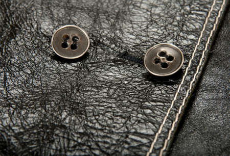 Close-up of metal buttons on shiny black leather clothing.