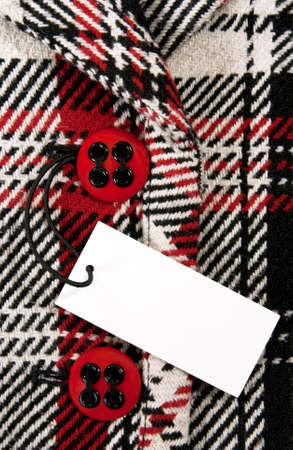Blank label or price tag attached to a button of a stylish red checked coat. photo