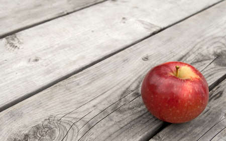 Red apple on gray old wooden table, with copy space. photo