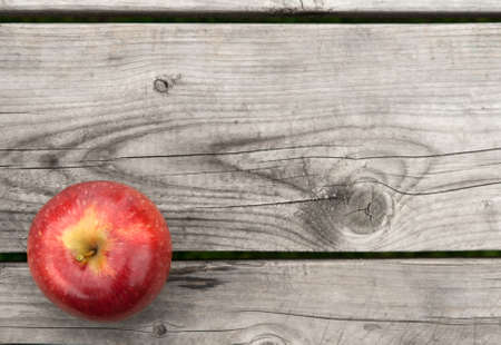 Red apple on gray old wooden table from above, with copy space. photo