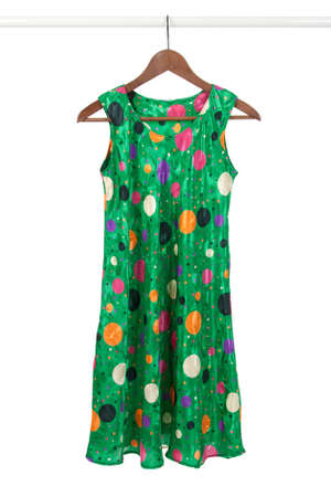 closet: Bright green funky dress on a wooden hanger, isolated on white. Stock Photo