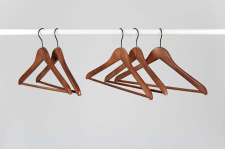 Wooden hangers on a rod, on a neutral gray background. Stock Photo