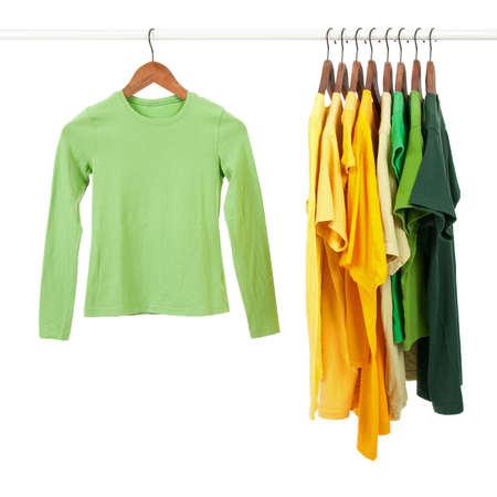 ropa colgada: Camisetas casuales de verdes y amarillos en perchas de madera, aisladas en blanco.  Foto de archivo