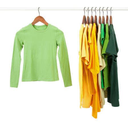 clothing rack: Green and yellow casual shirts on wooden hangers, isolated on white. Stock Photo