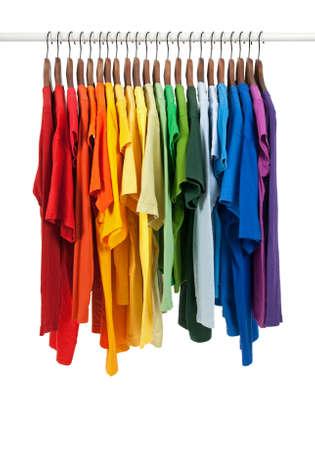 ropa colgada: Colores del arco iris. Variedad de camisetas casuales en perchas de madera, aisladas en blanco.