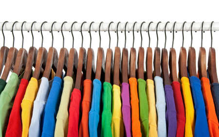 ropa colgada: Variedad de ropa casual multicolor en perchas de madera, sobre fondo blanco.  Foto de archivo