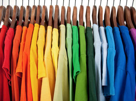 green clothes: Colors of rainbow. Variety of casual clothes on wooden hangers, isolated on white. Stock Photo