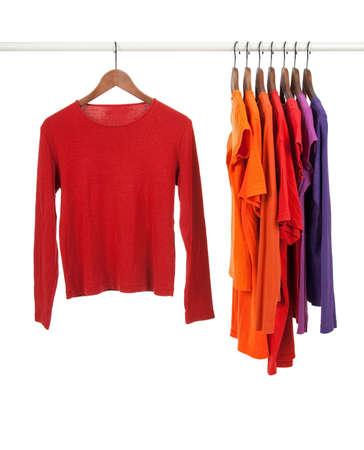 ropa colgada: Camisetas casuales rojos y p�rpuras en perchas de madera, aisladas en blanco.
