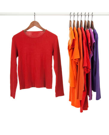 Red and purple casual shirts on wooden hangers, isolated on white.