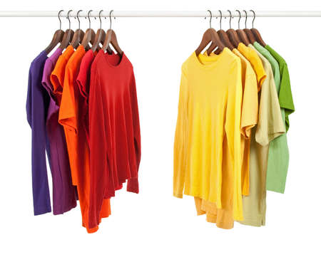 Choice of clothes of different colors on wooden hangers, isolated on white. Stock Photo