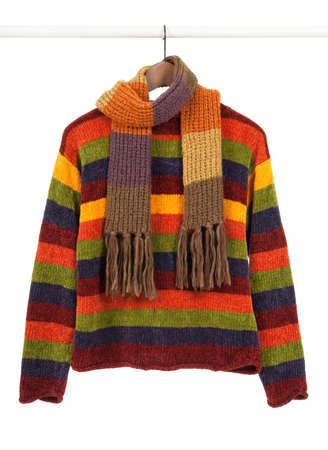 sueteres: Rayas colorido m�s dulce y bufanda en perchas de madera, aislados en blanco.  Foto de archivo