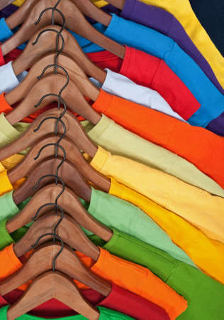 hangers: Choice of colorful casual clothes on wooden hangers. Stock Photo