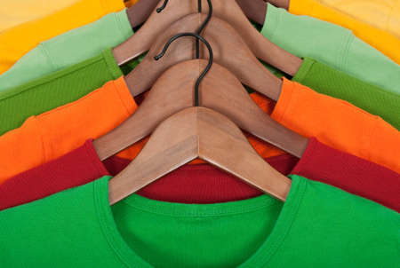 Choice of bright colorful t-shirts on wooden hangers. photo