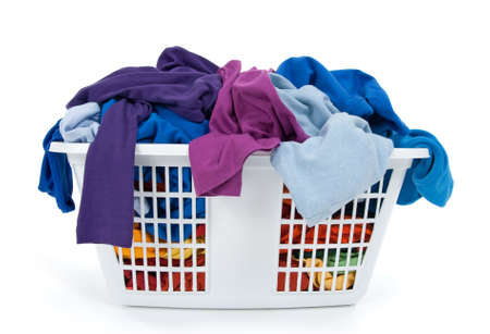 basket: Colorful clothes in a laundry basket on white background. Blue, indigo, purple. Stock Photo