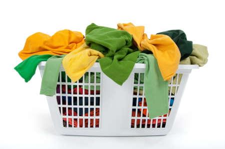 lavando ropa: Ropas coloridas en una canasta de lavander�a sobre fondo blanco. Verde, amarillo.  Foto de archivo
