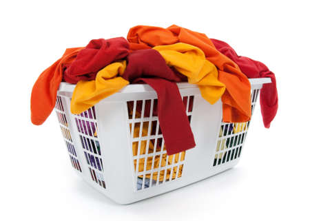 basket: Bright clothes in a laundry basket on white background. Red, orange, yellow. Stock Photo