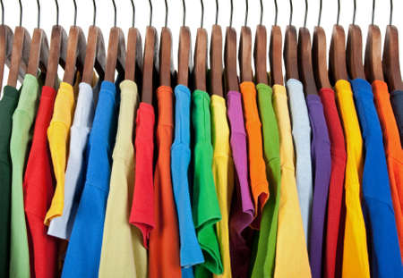 hangers: Variety of casual clothes of different colors on wooden hangers.