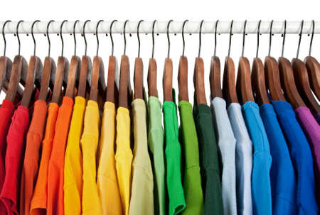 closet: Rainbow colors. Choice of casual clothes on wooden hangers, isolated on white.
