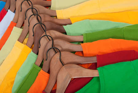 hangers: Many vibrant t-shirts of different colors on wooden hangers.