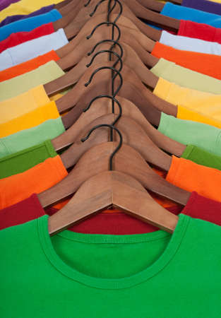 hangers: Choice of vibrant colorful t-shirts on wooden hangers.